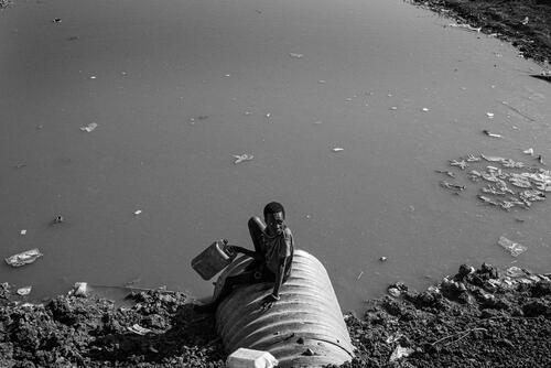 A young man sitting at the sewer inside the camp