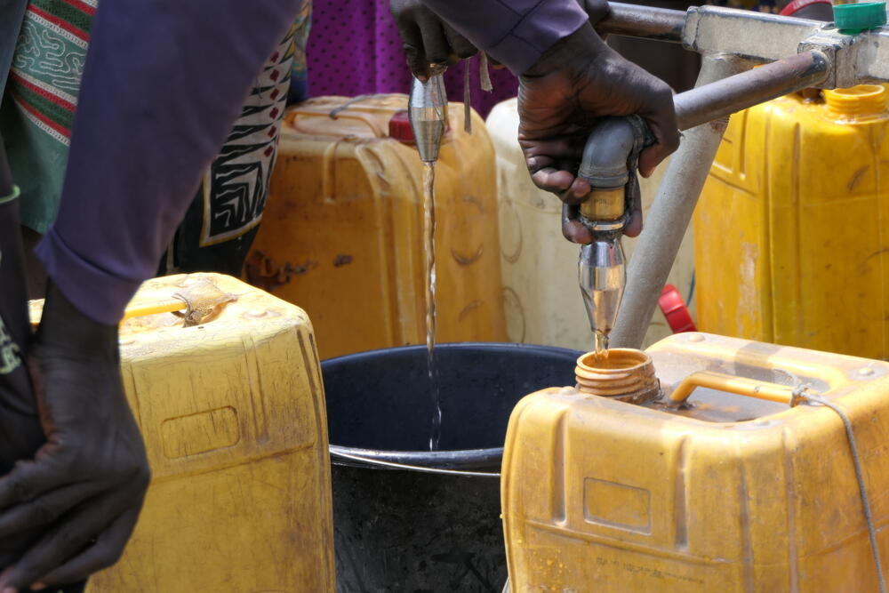 Residents of Bentiu camp filling containers at a water point