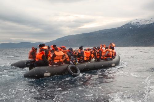 An overloaded boat carrying Syrian refugees is assisted to shore
