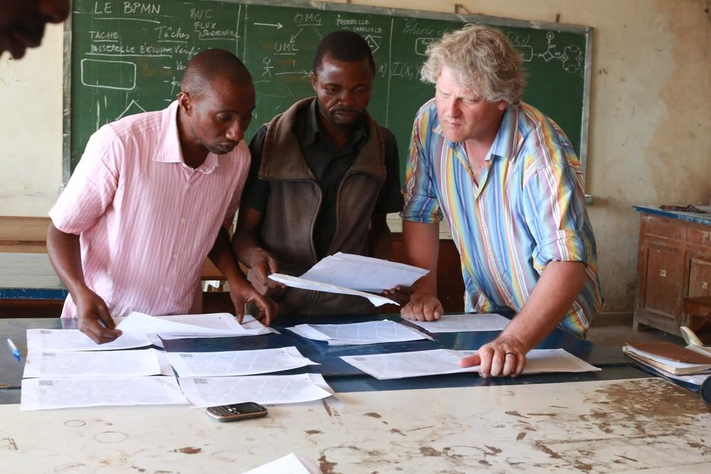 MSF staff and volunteers from the University of Lubumbashi, Democratic Republic of Congo, use a base map to trace information su