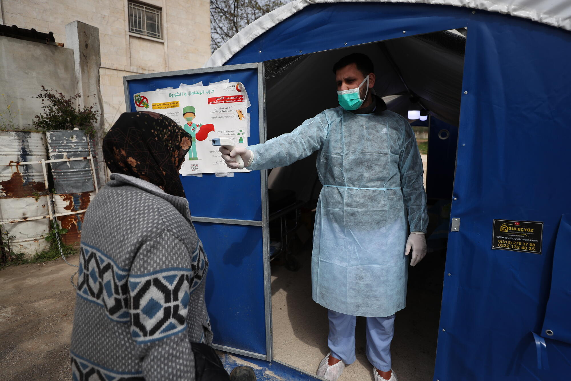 A doctor checks a patient's temperature outside an MSF-supported hospital in northwest Syria