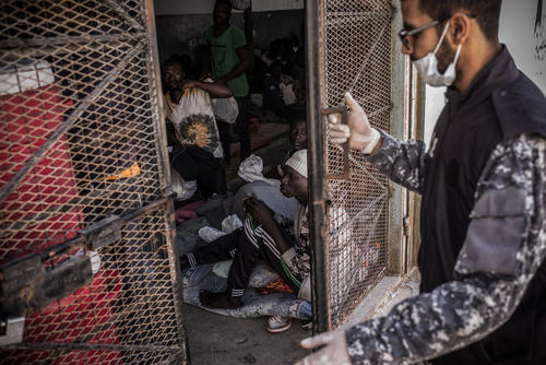 A guard shutting people in a detention centre cell in Tripoli, Libya, March 2017