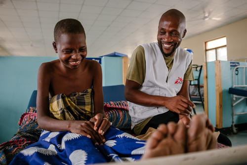 Esther, a patient with advanced HIV, shares a joke with MSF staff member Moses