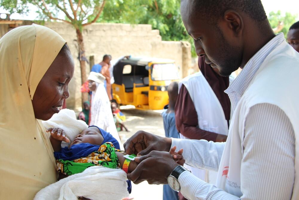 An MSF medic checks a child for signs of malnutrition at a displacement camp in Maiduguri, Nigeria