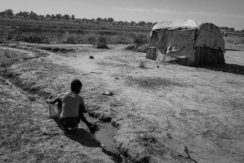A young boy collecting water in a small stream near the Bentiu camp