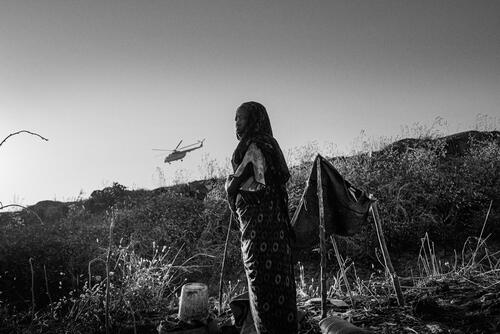 A young girl working in her small garden inside the camp while a United Nations helicopter takes off nearby