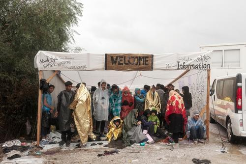 Refugees take shelter during a rainstorm over Moria
