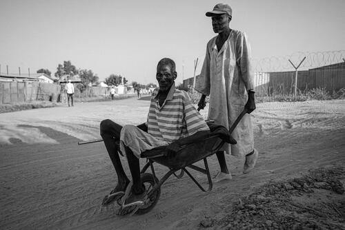 A man uses a wheelbarrow to transport a sick man to the MSF hospital in Bentiu