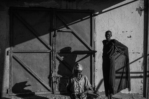Families outside their shelter at an abandoned shop in Bentiu town