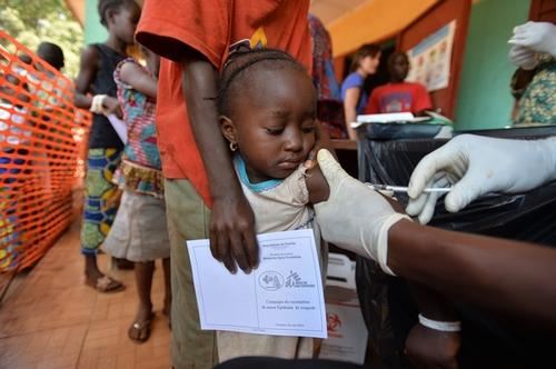 MSF staff member vaccinates a child against measles in Conakry, Guinea