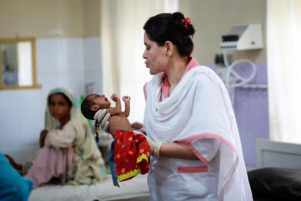 An MSF nurse calms a malnourished baby in Balochistan, Pakistan