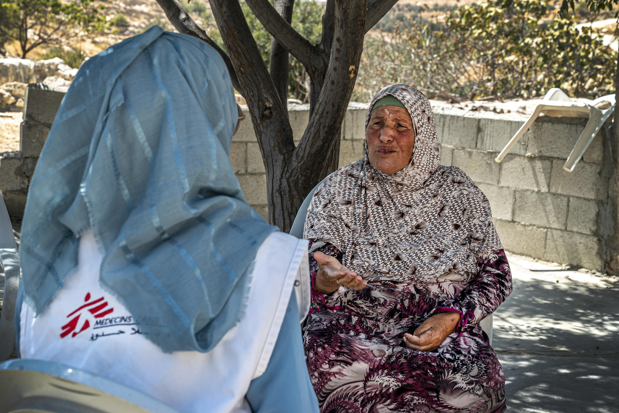 Fatima, a grandmother living in the West Bank, speaks to a member of MSF staff