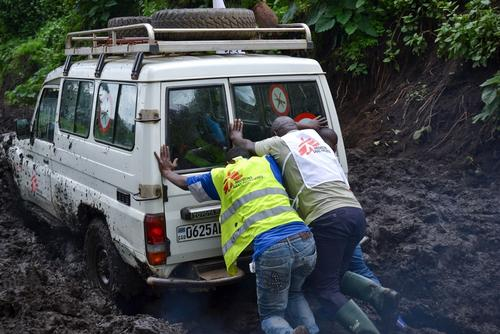 Medecins Sans Frontiers (MSF) staff members push the Land Cruiser out of the mud on the way to Remeka, DRC