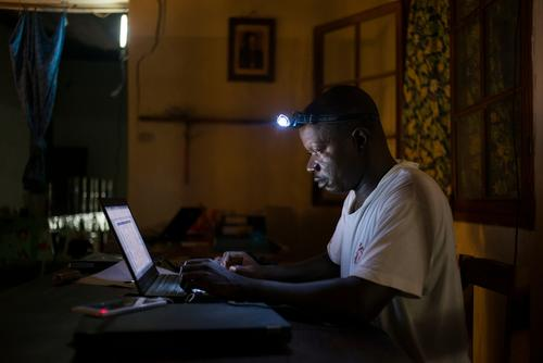 Jean Liyolongo, Head of Monga Intervention, works late into the night using a laptop and a head torch
