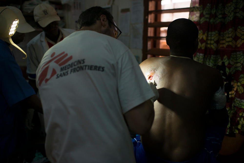 Doctor Victor Fayette (MSF) is treating Mahamat Sale's wound at Bria hospital