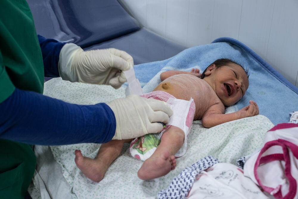 An MSF midwife puts a nappy on a baby in MSF's maternity clinic in Domiz refugee camp, Iraq