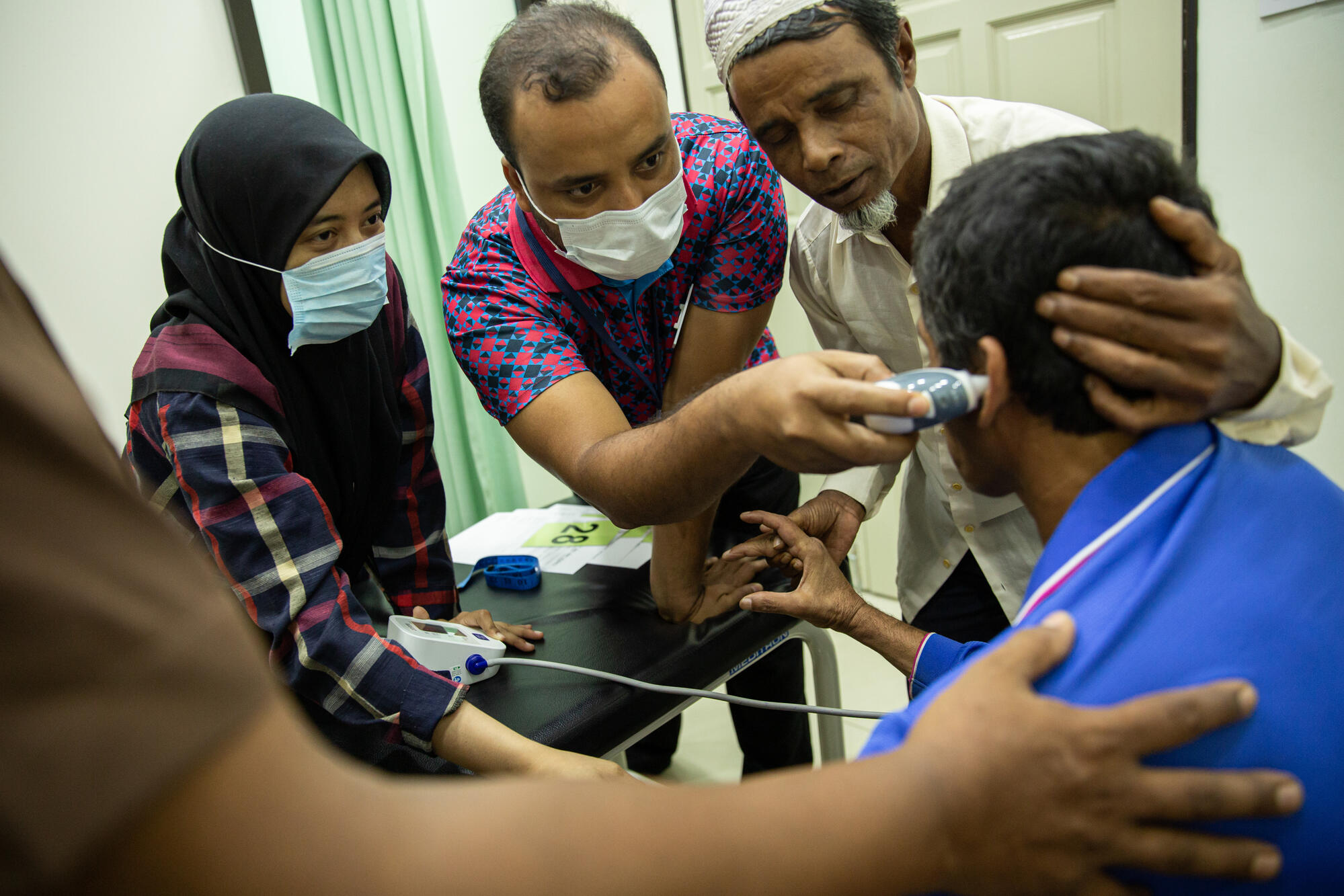 Kairul, a Rohingya refugee is examined by MSF nurses after falling two floors while working at a construction date