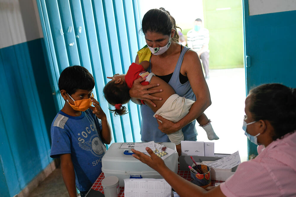 Noble Garcia brings her grandson, who has symptoms of malaria, to the MSF clinic in San Vicente