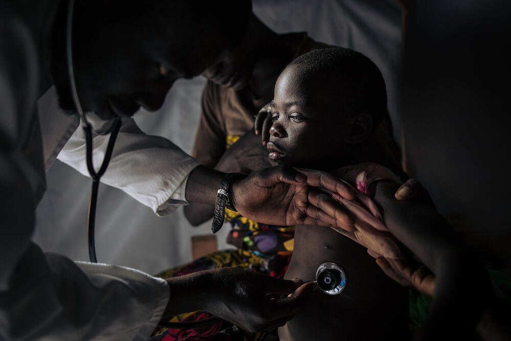 An MSF medic examines a five year old child at the Measles Unit in Biringi Hospital, Ituri, DRC