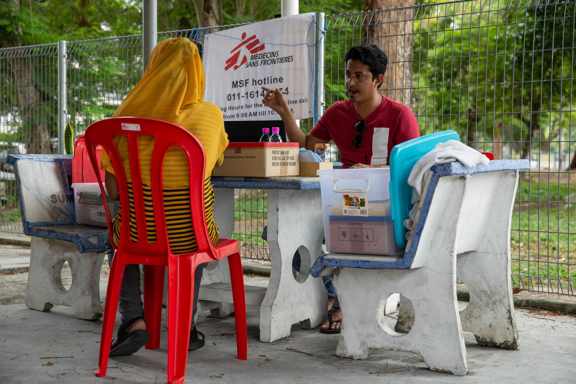 An MSF staff member registers a patient outside the MSF mobile clinic in Bukit Gudung, Penang.