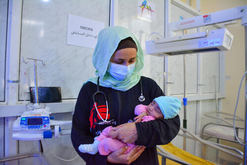 MSF paediatrician Monica Costeira holding a baby in the neonatal unit of Al-Qanawis Hospital in Yemen