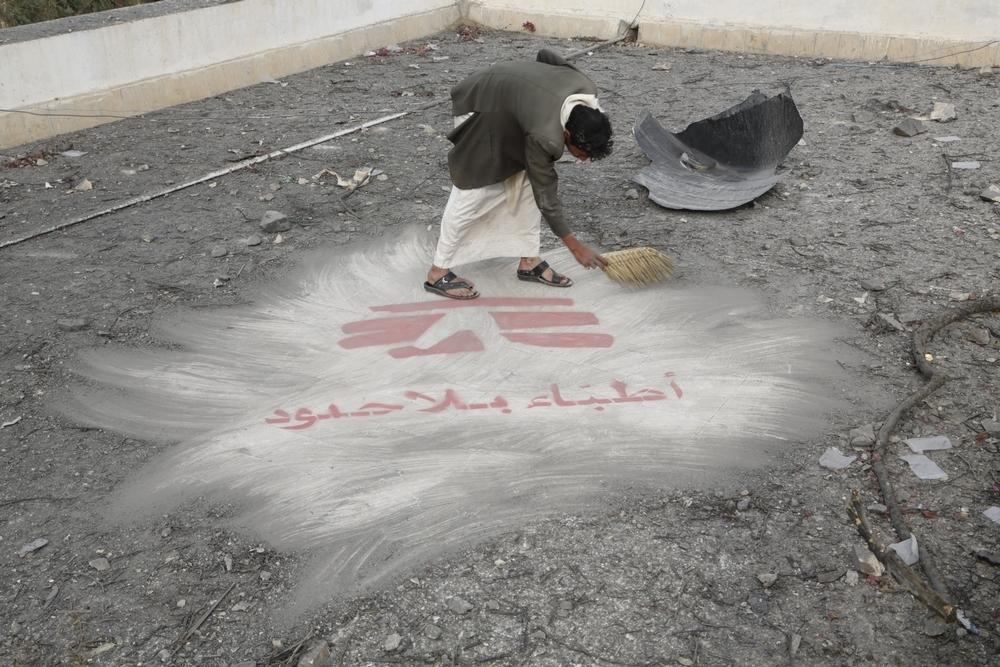 A man clears debris revealing the Médecins Sans Frontières logo  painted on the roof of the hospital in Haydan, Yemen