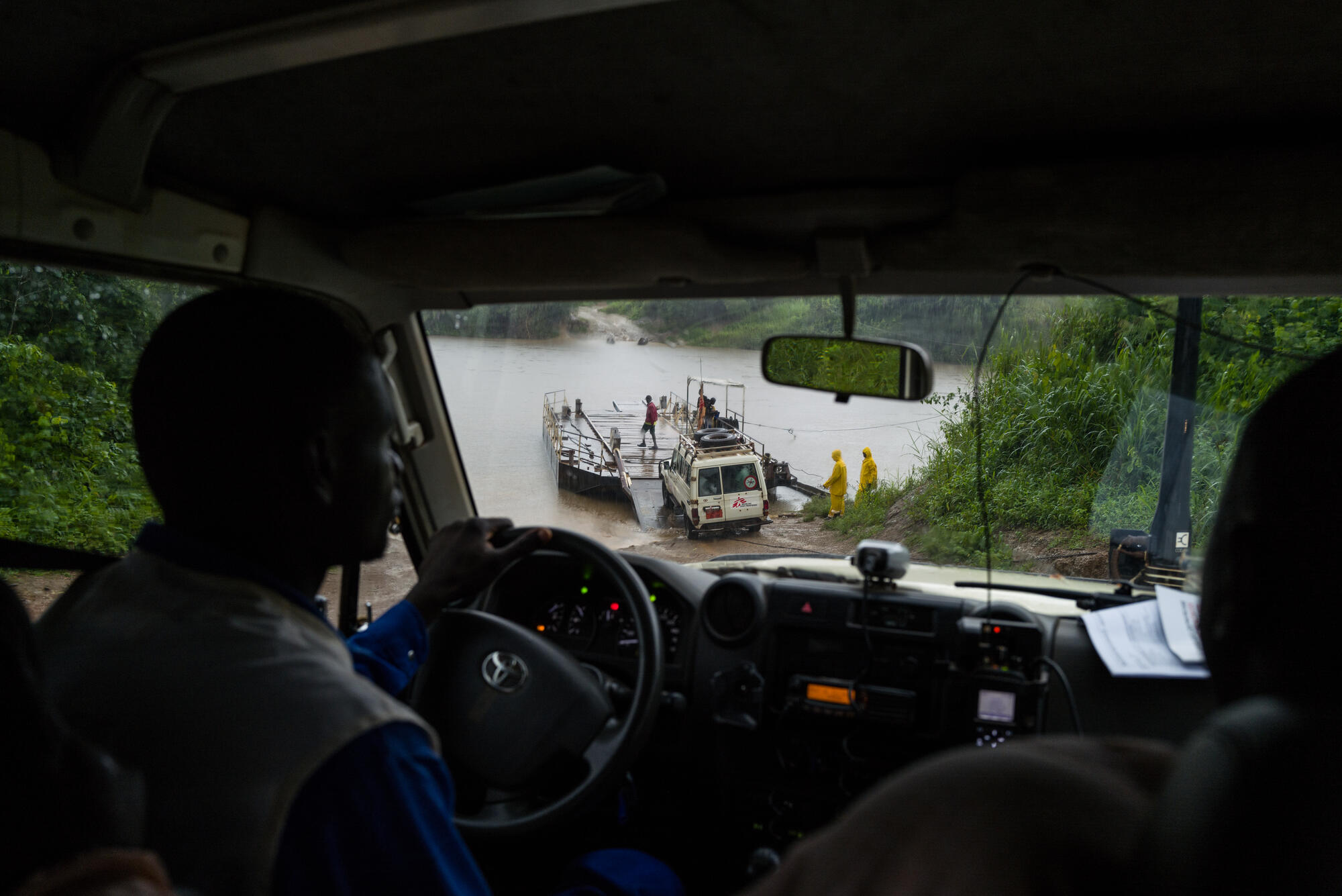 MSF vehicles ride the cable ferry to cross the river on the way to Nzacko