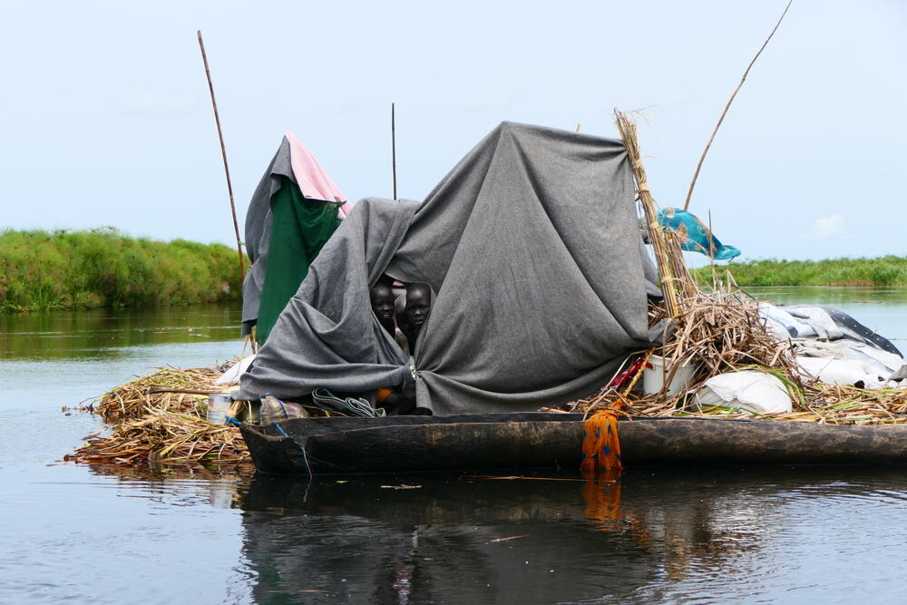 A displaced family using blankets and plastic sheeting to build a shelter on a grass raft