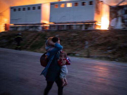 A woman flees a fire at Moria refugee camp – Lesvos, Greece, 9 September 2020
