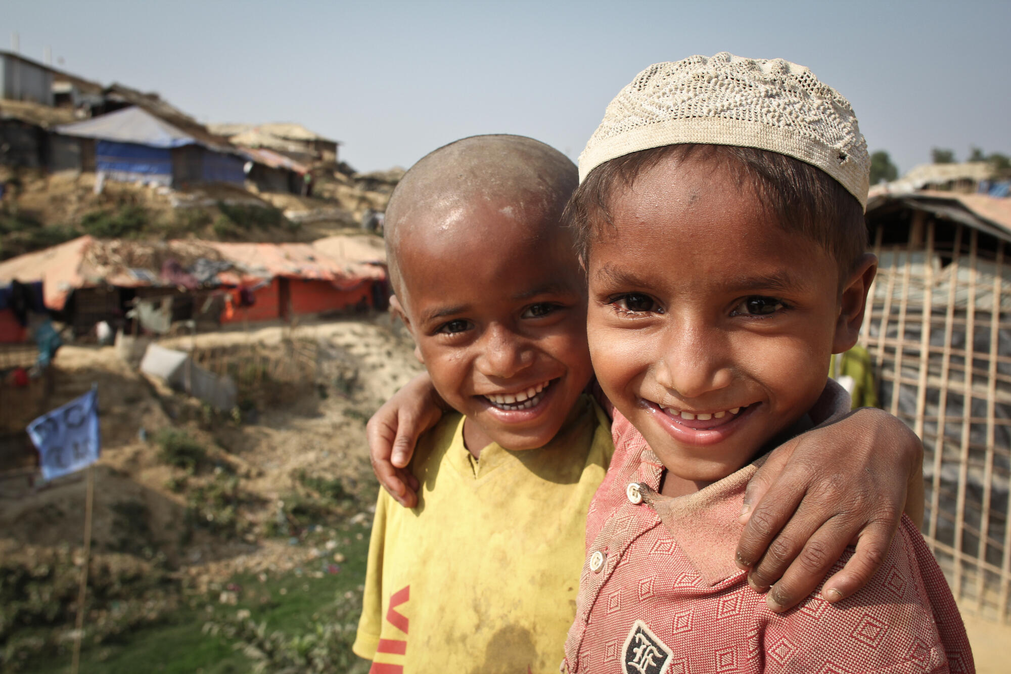 Two children smiling as they walk through the hot and dusty streets of Kutupalong makeshift camp in Cox's Bazar district.