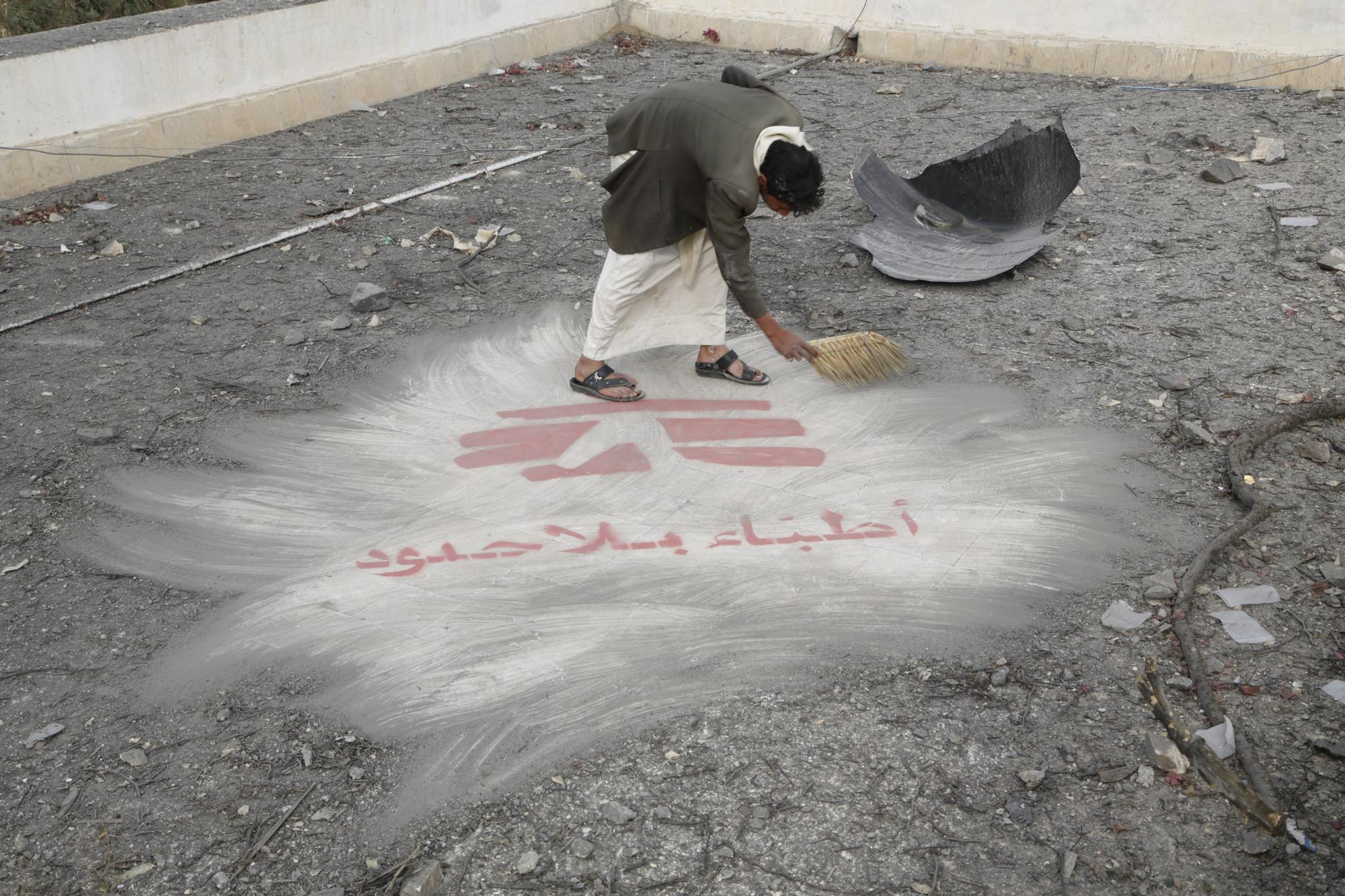 A man sweeping away dirt from an MSF logo at his feet.