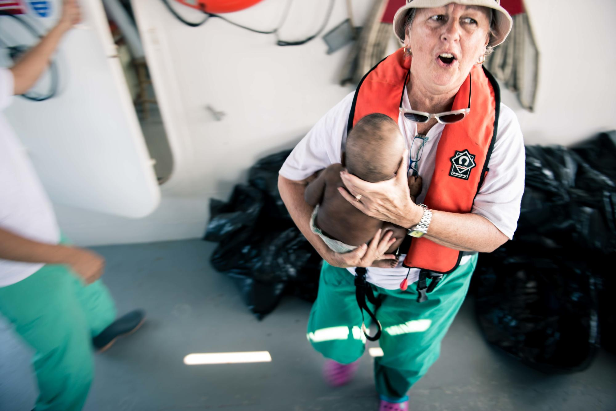 An MSF worker on a ship wearing a life jacket holds a small baby.
