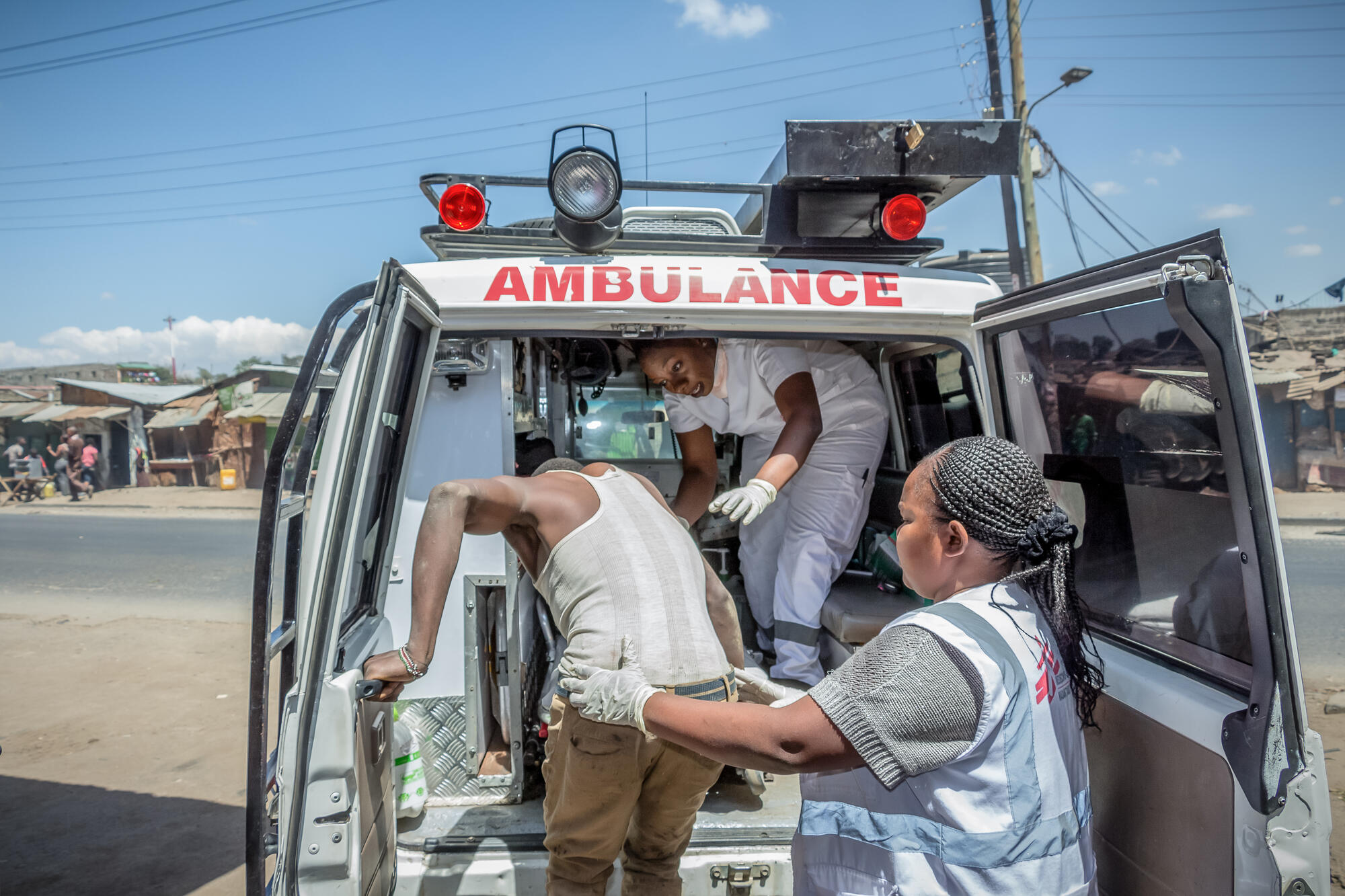 MSF staff help a patient into an ambulance in Nairobi