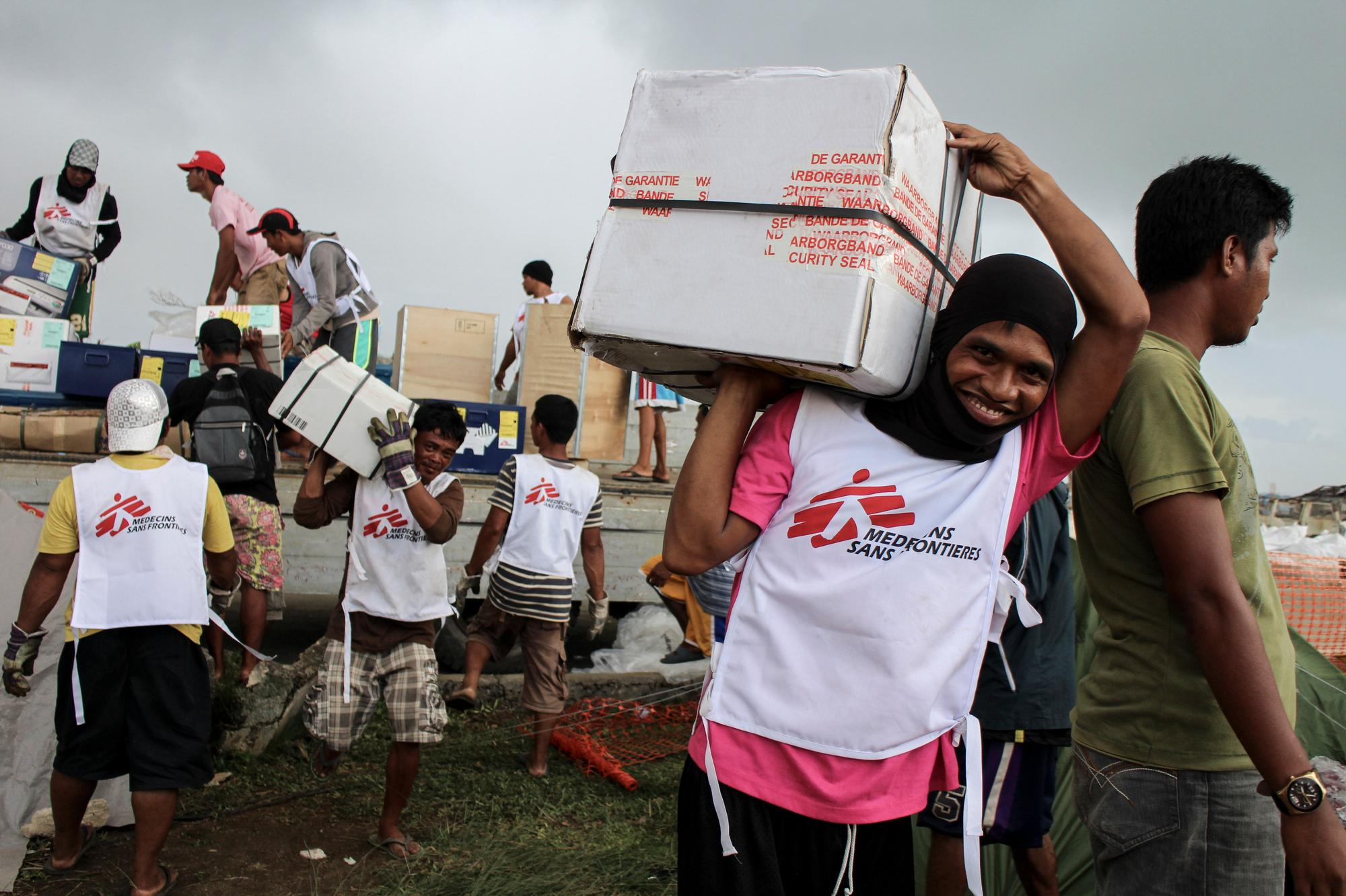 MSF workers smiling and carrying supply boxes away from a truck.
