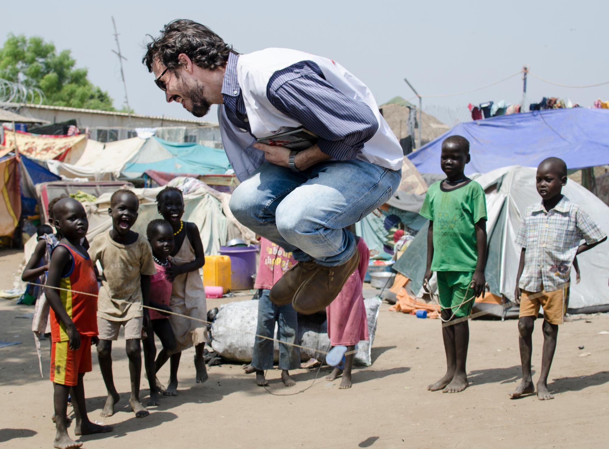An MSF worker jumps over a skipping rope as smiling children look on.