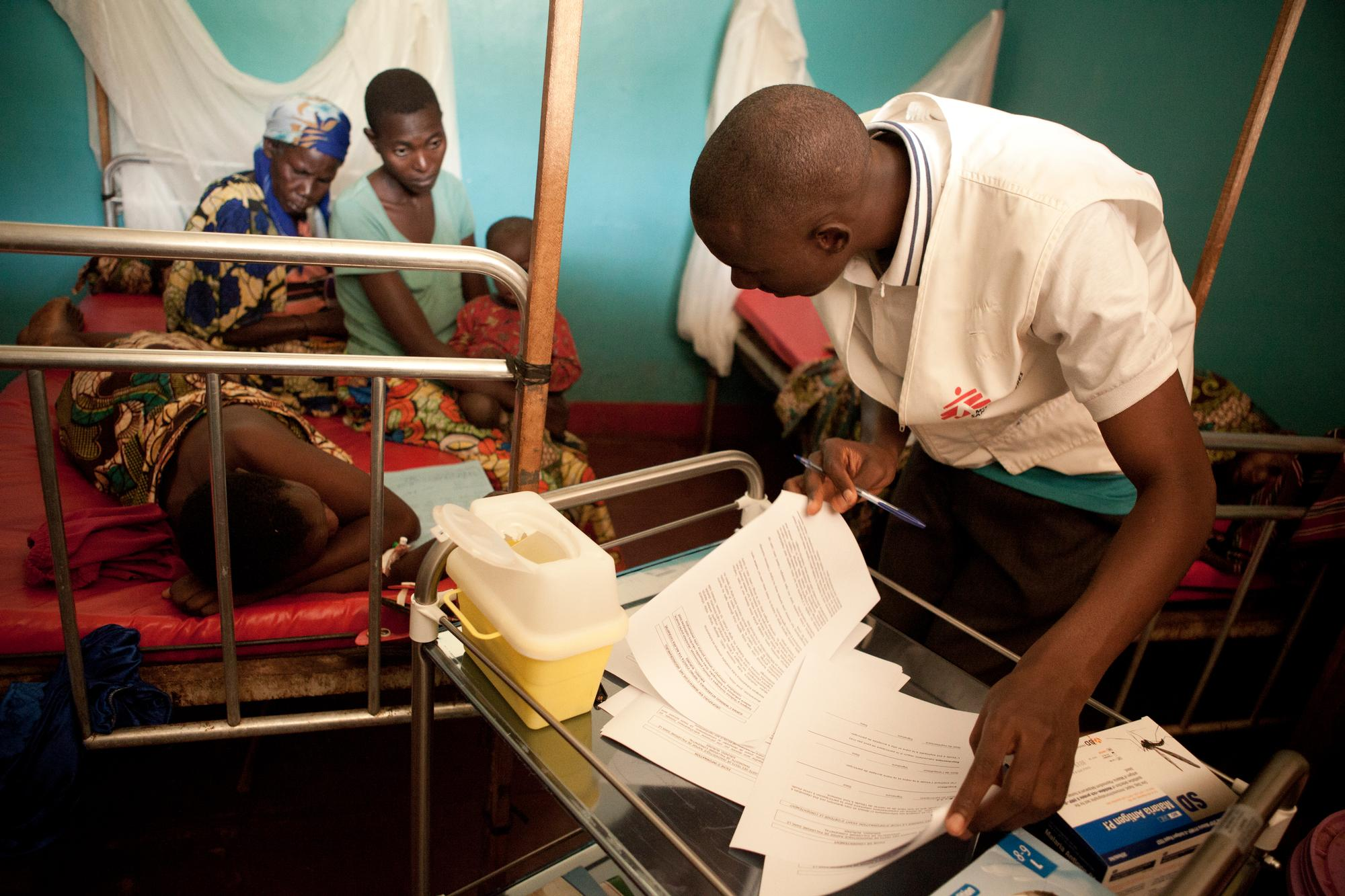 An MSF health worker, flipping through papers, leans down to a patient lying on a bed, as two women and a child sitting on the bed look on.