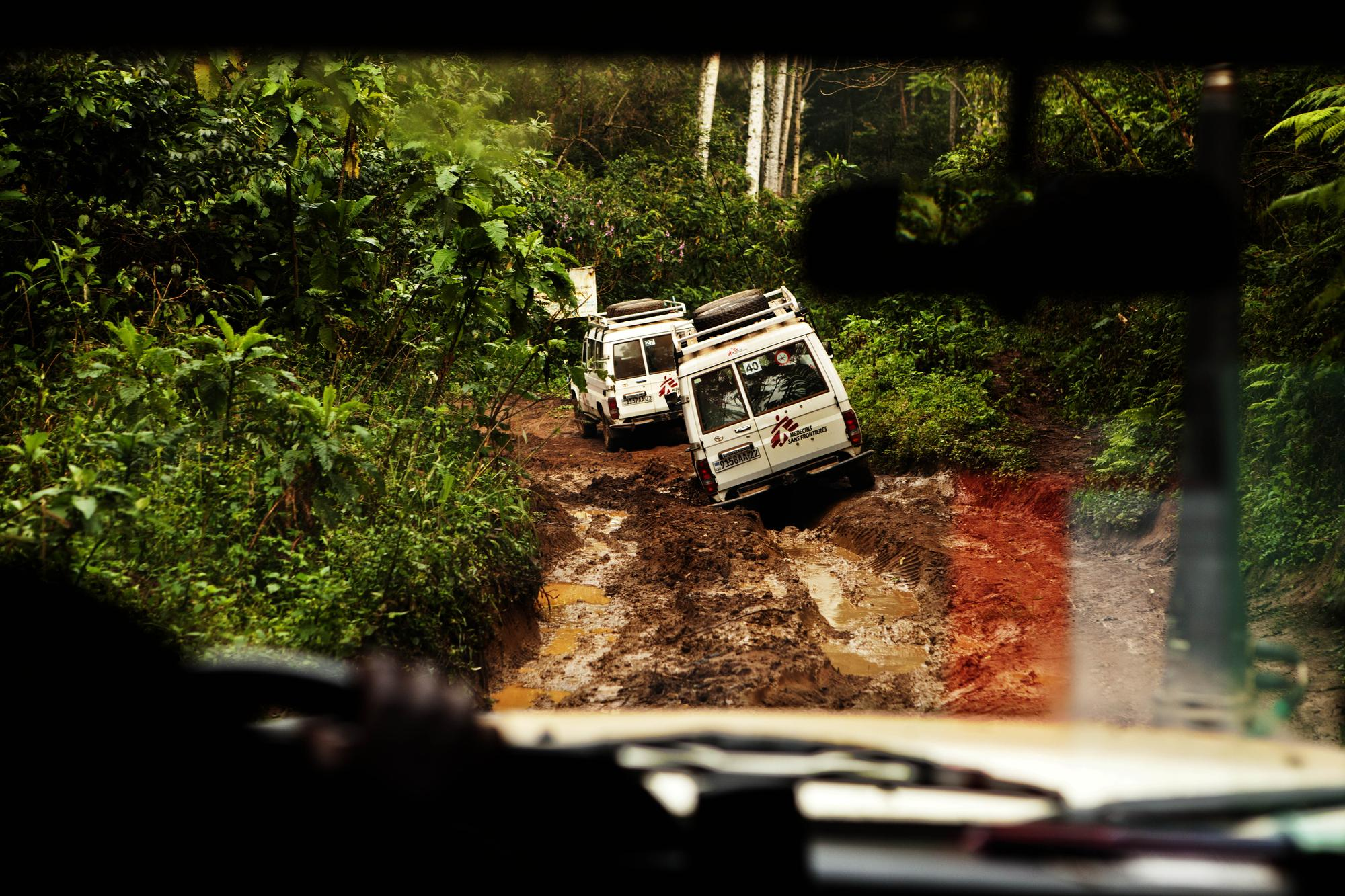 Looking out a windscreen, two all-terrain vehicles make their way along a muddy road.