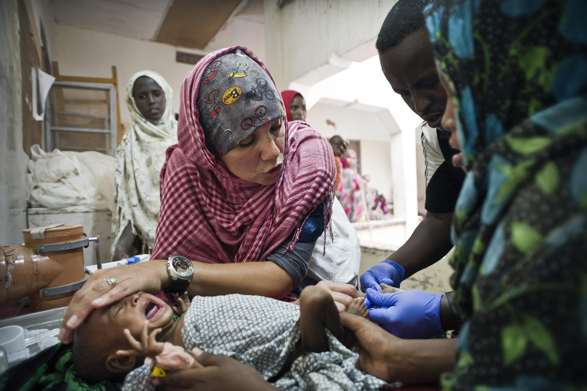 Somalia: A severely malnourished child is given an intravenous line.