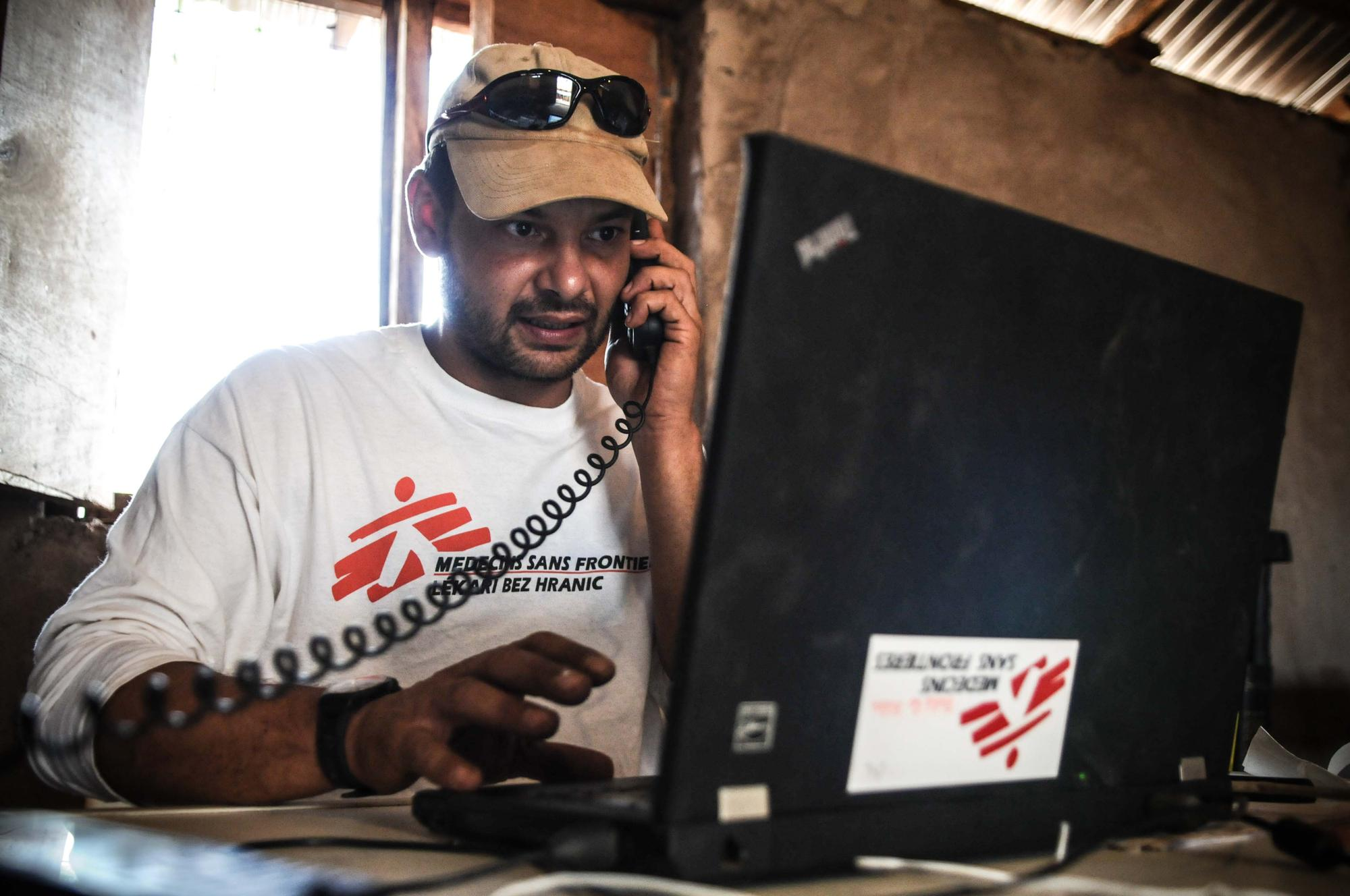 Man wearing MSF shirt sitting at a laptop and talking on the phone.