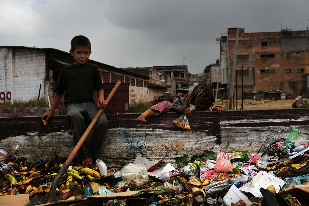 Children work in a dumpster near the shack they live in in Tegucigalpa, Honduras