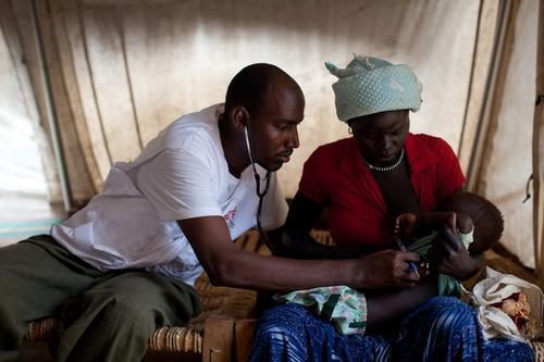 Un oficial clínico de MSF examina a un joven paciente en el hospital de campo de MSF en el campamento de refugiados de Doro, en Sudán del Sur. MSF/Nichole Sobe