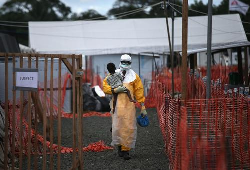 An MSF health worker carries a child suspected of having Ebola in an MSF treatment centre in Paynesville, Liberia, 2014.