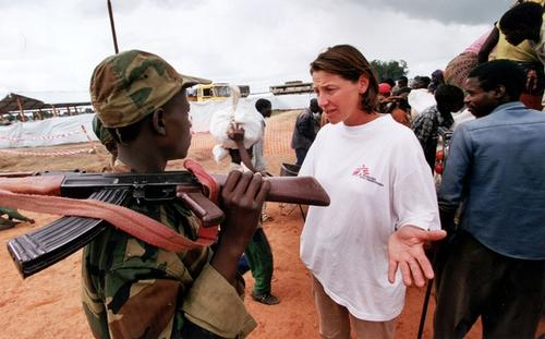 An MSF health worker discusses problems with an armed soldier in Angola.