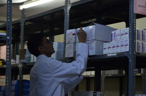 MSF pharmacy store keeper in Yemen checking stocks.