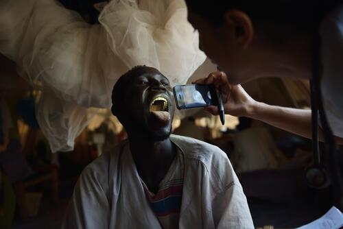 An MSF doctor uses a smartphone to examine a patient's throat.