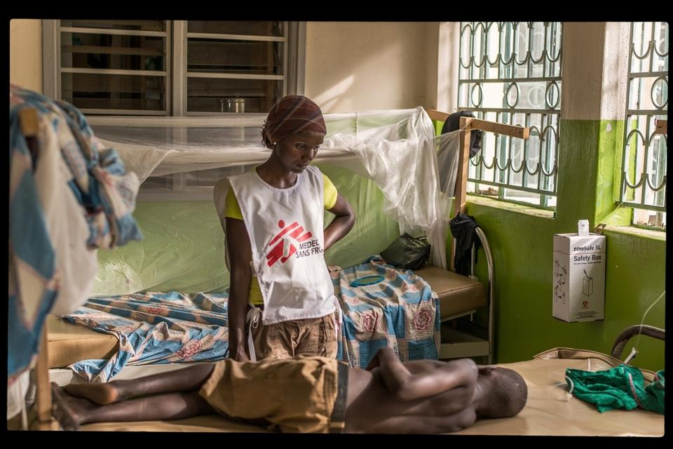 MSF Staff in Dzaipi Hospital Uganda standing at the bed of an ill boy
