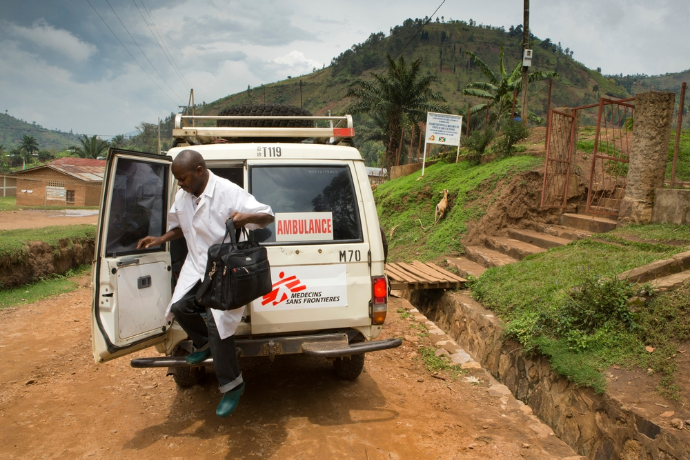 A Doctors Without Borders staff member exits an ambulance while carrying a bag filled with medical supplies.