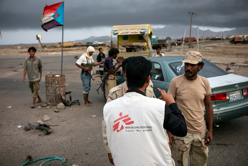 A Doctors Without Borders staff member speaking with armed men at a check point.