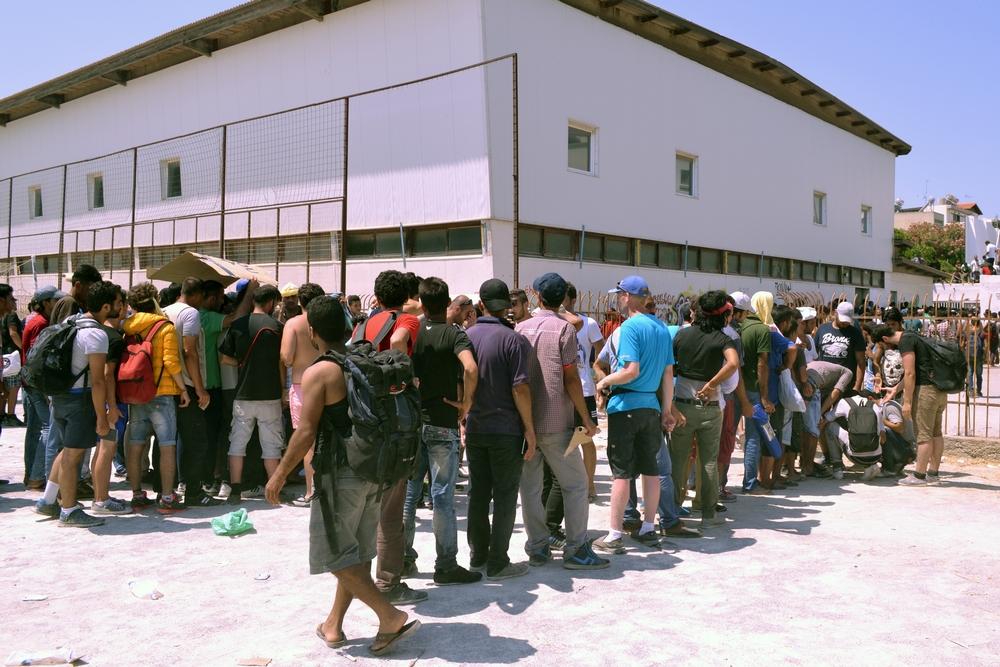 Lidé na stadionu musí čekat na registraci policií v dlouhých frontách na slunci.