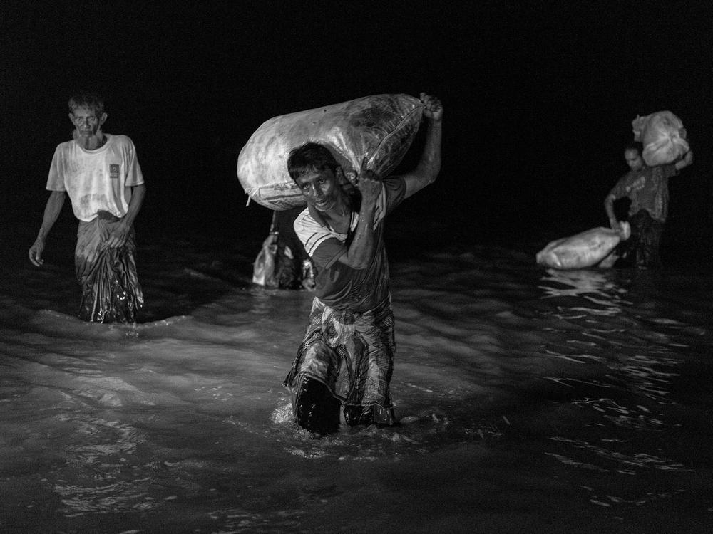 Rohingya refugees cross the Naf River from Myanmar into Bangladesh.